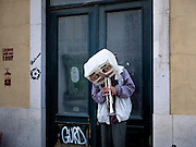 An immigrant from North Africa plays the trumpet, with is head covered by a mask, Rua Augusta, downtown Lisbon.This photograph is part of a body of work about Lisbon, feelings, affections and loneliness. Is about a city depressed by the crisis, but even so, tolerant and cosmopolitan. This part of Lisbon, the old town near the river Tejo (Tagus), with his deep character, where local people meets foreigners and alternative ways of life mixes with shamefaced poverty, is sublime by its peculiar light.