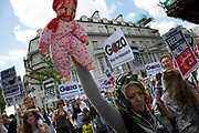 London, UK. Saturday 9th August 2014. Woman holding a bloody baby doll to signify the killing of children in Gaza. Pro-Palestinian protesters in their tens of thousands march through central London to the American Embassy in protest against the military offensive in Gaza by Israel. British citizens and British Palestinians gathered in huge numbers carrying placards and banners calling to 'Free Palestine' and to 'End the seige on Gaza'.