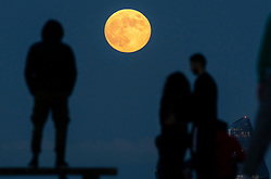 © Licensed to London News Pictures. 05/06/2020. London, UK. People watch from Primrose Hill as a spectacular full moon, known as the Strawberry Moon, rises over central London. Originally known as the Rose Moon in Europe the June full moon coincides with the strawberry harvest. Photo credit: Peter Macdiarmid/LNP