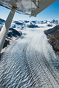 """Aerial view of McBride Glacier, in Glacier Bay National Park, in Alaska, USA. Flightseeing from Skagway or Haines is a spectacular way to see Glacier Bay. We were bedazzled by Mountain Flying Service's 1.3-hour West Arm tour from Skagway. Glacier Bay is honored by UNESCO as part of a huge Biosphere Reserve and World Heritage site shared between Canada and the United States. In 1750-80, Glacier Bay was totally covered by ice, which has since radically melted away. In 1794, Captain George Vancover found Icy Strait on the Gulf of Alaska choked with ice, and all but a 3-mile indentation of Glacier Bay was filled by a huge tongue of the Grand Pacific Glacier, 4000 feet deep and 20 miles wide. By 1879, naturalist John Muir reported that the ice had retreated 48 miles up the bay. In 1890, """"Glacier Bay"""" was named by Captain Beardslee of the U.S. Navy. Over the last 200 years, melting glaciers have exposed 65 miles of ocean. As of 2019, glaciers cover only 27% of the Park area. Since the mid 1900s, Alaska has warmed 3 degrees Fahrenheit and its winters have warmed nearly 6 degrees. Human-caused climate change induced by emissions of greenhouse gases continues to accelerate warming at an unprecedented rate. Climate change is having disproportionate effects in the Arctic, which is heating up twice as fast as the rest of Earth."""