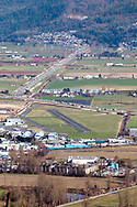 View of Trans Canada Highway and the Chilliwack Municipal Airport (YCW)  in Chilliwack, British Columbia, Canada. The Trans Canada Highway (Highway 1) winds through the farmland next to the Chilliwack Airport during a late winter day.  Photographed from Hillkeep Regional Park on Chilliwack Mountain.