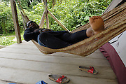 Ecuador, May 9 2010: Lorna relaxes in a hammock near the river. Copyright 2010 Peter Horrell