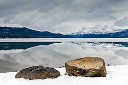 A stormy promise of spring, the ice melting off Payette Lake during a rain storm of April.  The still waters of the lake reflecting the storm above and the mountains beyond. You can find Payette Lake in the town of McCall Idaho