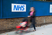 Person walks past a sign for the NHS or National Health Service in London, UK. The National Health Service (NHS) is the shared name of three of the four publicly funded healthcare systems in the United Kingdom. The systems are primarily funded through general taxation rather than requiring insurance payments, and were founded in 1948. They provide a comprehensive range of health services, the vast majority of which are free at the point of use to residents of the United Kingdom.