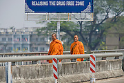 """26 FEBRUARY 2008 -- MAE SOT, TAK, THAILAND: Buddhist monks cross the Thai-Myanmar Friendship Bridge into Myawaddy, Myanmar from Mae Sot, Thailand. There are millions of Burmese migrant workers and refugees living in Thailand. Many live in refugee camps along the Thai-Burma (Myanmar) border, but most live in Thailand as illegal immigrants. They don't have papers and can not live, work or travel in Thailand but they do so """"under the radar"""" by either avoiding Thai officials or paying bribes to stay in the country. Most have fled political persecution in Burma but many are simply in search of a better life and greater economic opportunity.  Photo by Jack Kurtz"""
