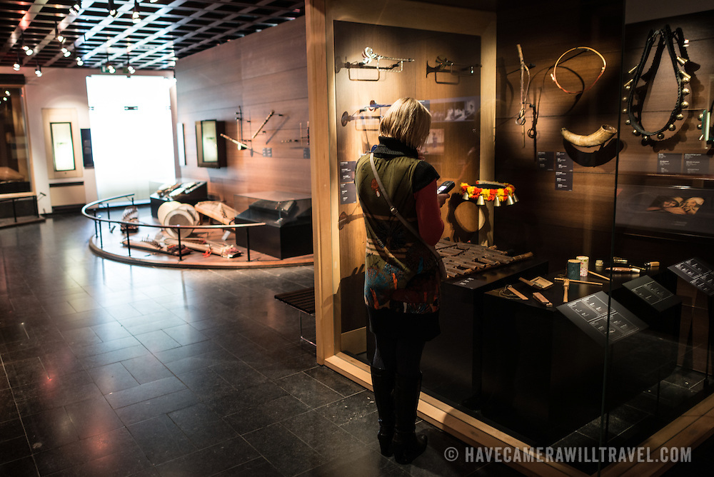 A visitor looks at a display case of various cultural instruments from around the world on display at the Musical Instrument Museum in Brussels. The Musee des Instruments de Musique (Musical Instrument Museum) in Brussels contains exhibits containing more than 2000 musical instruments. Displays include historical, exotic, and traditional cultural instruments from around the world. Visitors to the museum are given handheld audio guides that play musical demonstrations of many of the instruments. The museum is housed in the distinctive Old England Building.