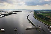 Nederland, Noordoostpolder, Flevoland, 30-06-2011. Ramspol, Waterkering Kampen, tussen Ketelmeer en Zwarte Water. Links Ramsdiep en Noordoostpolder. De balgstuw is een stormvloedkering en bestaat uit een opblaasbare dam of dijk, opgebouwd uit drie balgen. In niet-opgeblazen toestand liggen de balgen op de bodem..Naast de stuw grondwerk voor de nieuwe dubbelbaans Ramspolbrug..Ramspol, inflatable dike, between Ketelmeer and Black Water. The Balgstuw (bellow barrier) is a storm barrier and consists of an inflatable dam or dyke, composed of three bellows. Usually, each bellow rests on the bottom of the water...luchtfoto (toeslag), aerial photo (additional fee required).copyright foto/photo Siebe Swart