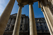 Bank of England  seen through rising pillars and columns of Cornhill Exchange, City of London. We look upwards to the famous Bank of England in the City Of London, the financial district, otherwise known as the Square Mile. With such a wide-angle perspective the bank and its architecture looks powerful and influencial in the UK's economy. The tall pillars rise above and makes for a scene of stability and strength.
