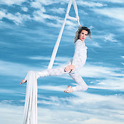 Female Aerialist acrobat performs in the air on fabric with a blue sky background