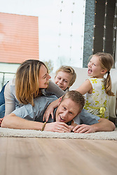 Happy family with two kids at home, lying on floor