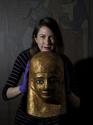 An exhibition at the National Museum of Scotland tells the story of one ancient Egyptian tomb across 1,000 years of use. Built around 1290 BC, the tomb was reused a number of times before being sealed in the 1st Century AD and left undisturbed until its excavation in the 19th Century<br /> <br /> Pictured: Dr Margaret Maitland, Senior Curator, Ancient Mediterranean at National Museums of Scotland with  Mummy-mask of Montsuef