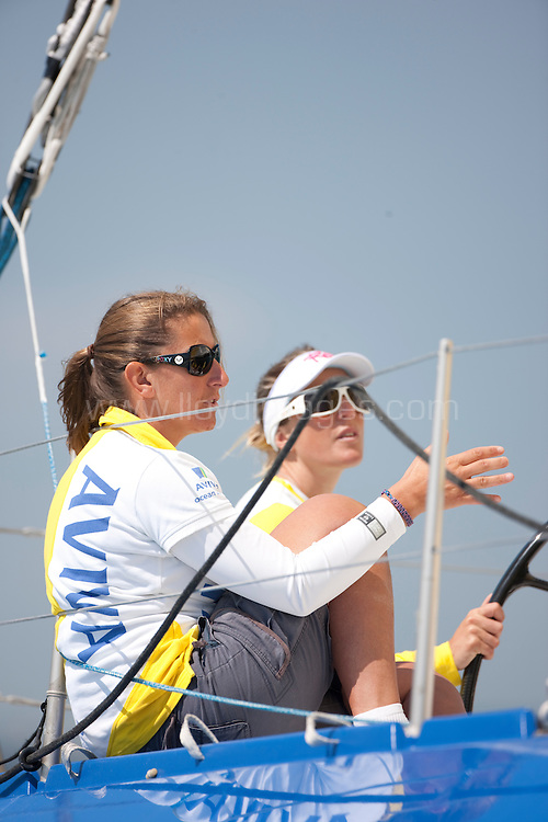"""Dee Caffari and her IMOCA Open 60 """"Aviva"""" shown here training in the Solent with an all female crew, including fellow British yachtswoman and Vendée Globe race rival Sam Davies (GBR),Miranda Merron (GBR) and boat captain Alex Sizer(GBR) and German Figaro sailor Isabelle Joschke...The team are preparing to challenge the outright record to sail around Britain and Ireland in a monohull yacht stands, at 7 days 4 hours Set in May 2004 onboard Solune. The record for an all-female crew stands at 10 days and 16 hours, which was set by Sam Davies and her crew onboard Roxy in June 2007...Credit all pictures:Lloyd Images.."""
