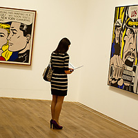London, UK - 18 February 2013: a woman stands between 'Torpedo...Los!' and 'Masterpiece' during the  'Lichtenstein: A Retrospective' exhibition that opens at Tate Modern in London on the 21st of February. The exhibition is the first major Lichtenstein retrospective for twenty years, bringing together over 125 of the artist's most definitive paintings and sculptures. Built on new research and scholarship, the exhibition reassesses Lichtenstein's work and his enduring legacy.