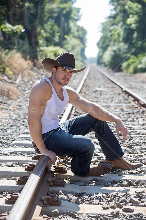 sexy cowboy on a railroad track