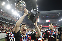 Raphael Veiga of Brazil's Atletico Paranaense celebrates with the trophy after defeating Colombia's Junior in the Copa Sudamericana final soccer match at the Arena da Baixada stadium in Curitiba, Brazil, Thursday, Dec. 13, 2018. Atletico Paranaense beat Junior 4-3 on penalties after the match ended 1-1 after extra time. (AP Photo/Andre Penner)