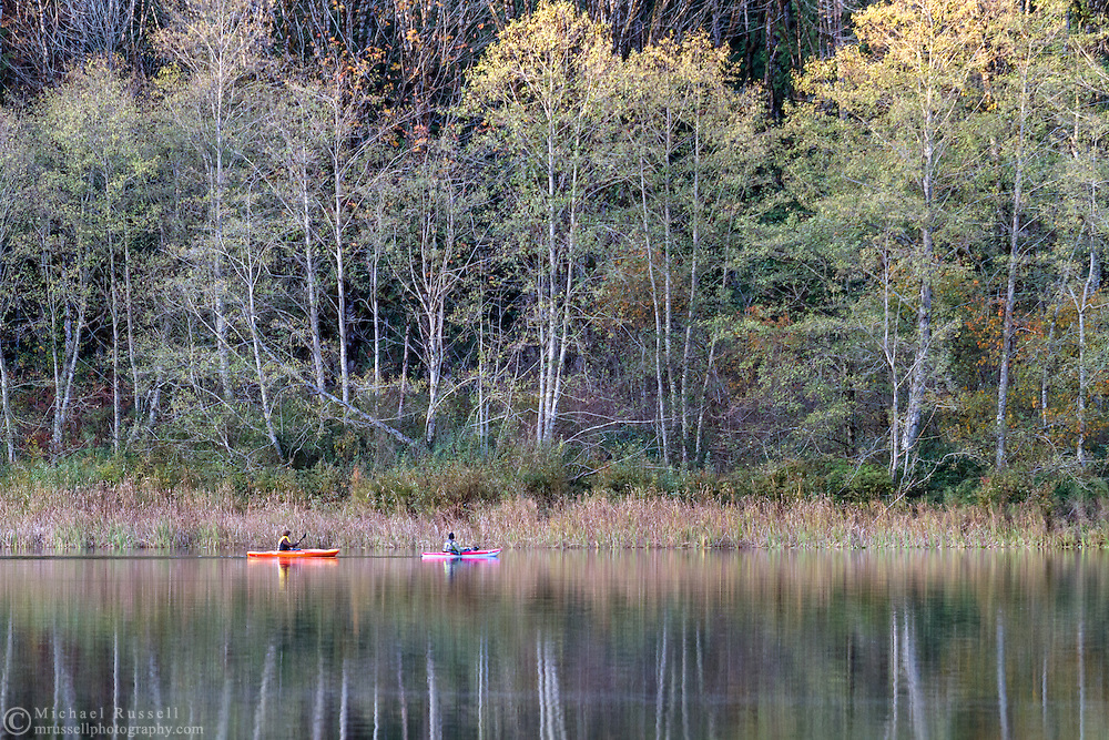 Two kayakers paddle along the shore of Deer Lake in Sasquatch Provincial Park, British Columbia, Canada.