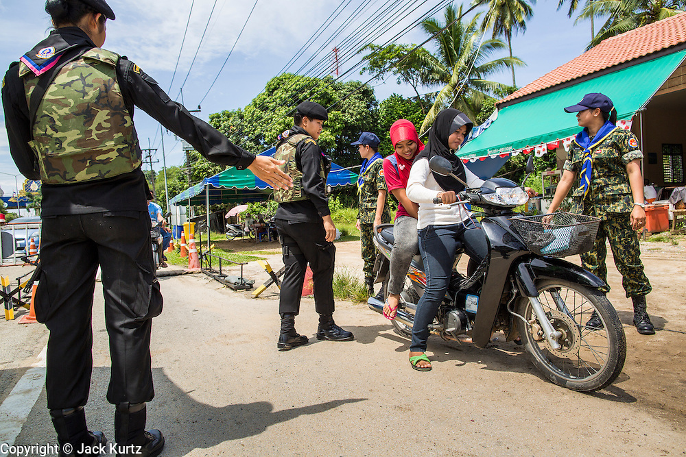"""25 OCTOBER 2012 - TAK BAI, NARATHIWAT, THAILAND: Thai women Rangers (paramilitary operating under Army command) pull over Muslim women at a checkpoint in Tak Bai, Thailand. The """"Tak Bai Incident"""" took place on Oct. 25 in Tak Bai, Narathiwat, Thailand during the Muslim insurgency in southern Thailand. On that day, a crowd gathered to protest the arrest of local residents. Police made hundreds of arrests during the protest and transported the arrested to Pattani, about two hours away, in another province. They were transported in locked trucks and more than 80 people suffocated en route. This enraged local Muslims and shocked people across Thailand. No one in the Thai army accepted responsibility for the deaths and no one was ever charged. In the past, the anniversary of the incident was marked by protests and bombings. This year it was quiet. More than 5,000 people have been killed and over 9,000 hurt in more than 11,000 incidents, or about 3.5 a day, in Thailand's three southernmost provinces and four districts of Songkhla since the insurgent violence erupted in January 2004, according to Deep South Watch, an independent research organization that monitors violence in Thailand's deep south region that borders Malaysia.   PHOTO BY JACK KURTZ"""