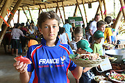 """Milan is 12 years old, son of Zach, who is a teacher at Green School, he is pictured with his wife Sophie Daubisse and youngest son Sevan-Fidel is 9 years old, who are students at Green School. They are french residents<br /><br />The Green School (Bali) is one of a kind in Indonesia. It is a private, kindergarten to secondary International school located along the Ayung River near Ubud, Bali, Indonesia. The school buildings are of ecologically-sustainable design made primarily of bamboo, also using local grass and mud walls. There are over 600 students coming from over 40 countries with a percentage of scholarships for local Indonesian students.<br /><br />The impressive three-domed """"Heart of School Building"""" is 60 metres long and uses 2500 bamboo poles. The school also utilizes renewable building materials for some of its other needs, and almost everything, even the desks, chairs, some of the clothes and football goal posts are made of bamboo.<br /><br />The educational focus is on ecological sustainability. Subjects taught include English, mathematics and science, including ecology, the environment and sustainability, as well as the creative arts, global perspectives and environmental management. This educational establishment is unlike other international schools in Indonesia. <br /><br />Renewable energy sources, including solar power and hydroelectric vortex, provide over 50% of the energy needs of the school. The school has an organic permaculture system and prepares students to become stewards of the environment. <br /><br />The school was founded by John and Cynthia Hardy in 2008."""
