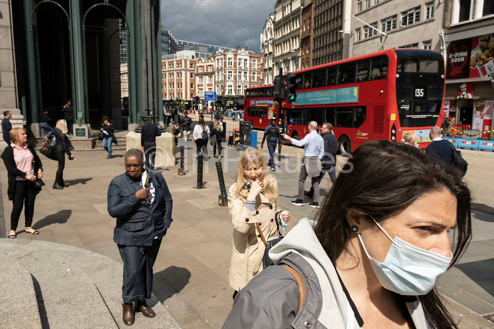 City workers, and commuters, many of whom are wearing face masks heading towards the entrance to Liverpool Street Station on Bishopsgate on 26th May 2021 in London, United Kingdom. As the coronavirus lockdown continues its process of easing restrictions, the City remains far quieter than usual, which asks the question if normal numbers of people and city workers will ever return to the Square Mile.