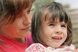 Mother sitting with young girl with autism,
