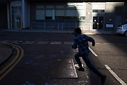 Child running through a shaft of evening light, casting a shadow of himself in East London, UK.