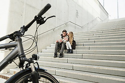 Young couple sitting on stairs and using a digital tablet, Munich, Bavaria, Germany