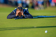 Bernd Wiesberger's caddy checks the line of a putt on the 18th green during the final round of the Aberdeen Standard Investments Scottish Open at The Renaissance Club, North Berwick, Scotland on 14 July 2019.