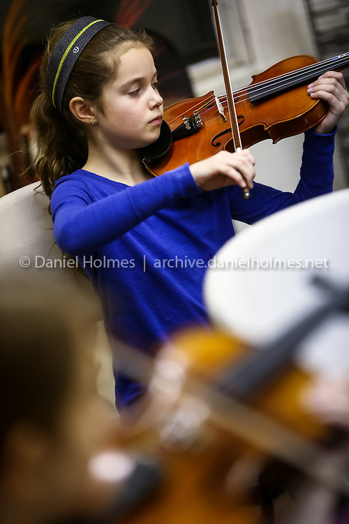 (1/12/15, NATICK, MA) Sophie Van Rhijfn, 8, of Natick, plays violin during the Natick Youth Orchestra rehearsal at the Debsan Building in Natick on Monday. Daily News and Wicked Local Photo/Dan Holmes