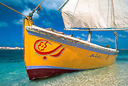 Egypt, 2000 -  A felucca rests on the shore of the beautifully colored Mediterranean.  Anchored in the shallow water, it waits to taxi passengers across the bay in Marsa Matrough. White sands, clear water and a rich blue sky accent the bright yellow boat.