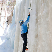 """Dan Hawes of Hanson, Massachusetts, climbs the frozen Champney Falls in the White Mountain National Forest. He uses 12 pointed crampons mounted on insulated plastic mountaineering boots, and an ice axe in each hand to aid her ascent of the waterfall. A rope attached to his climbing harness runs to an anchor at the top of the route, then down to his climbing partner and wife Jen Hawes (not shown), who guarantees that he is """"on belay: in case of a slip or fall."""