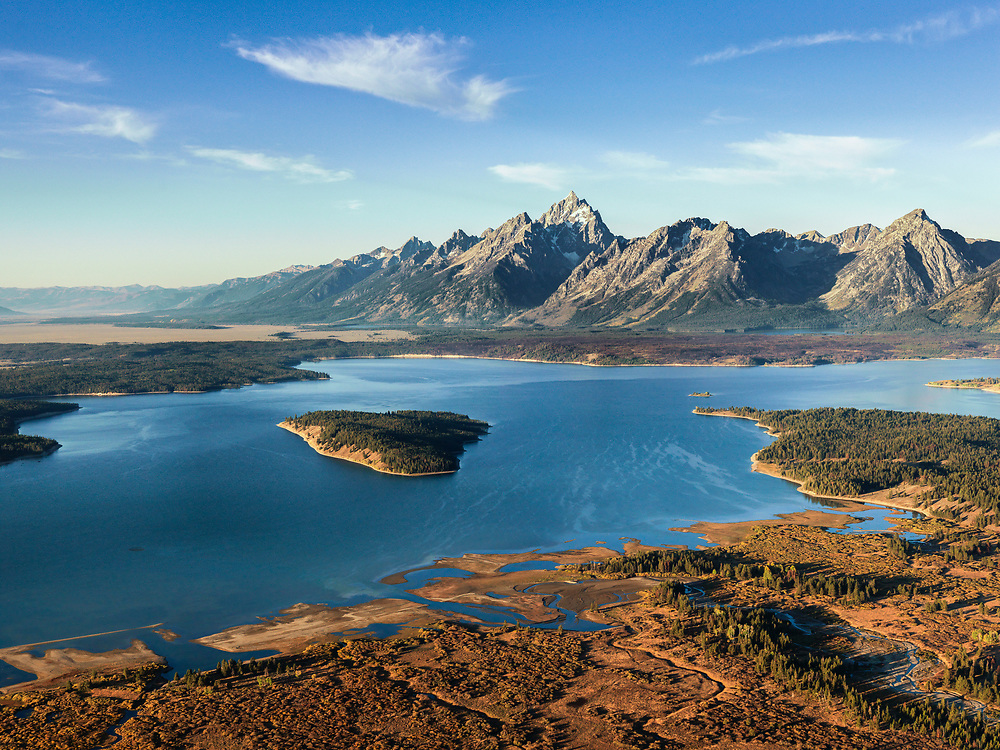 Autumn colors cover shoreline of Jackson Lake with the Grand Teton peak looming in background.<br /> Licensing and Open Edition Prints