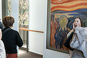 taking a picture with the Edvard Munch The Scream painting billboard at the retrospective exhibition in the Tokyo Metropolitan Art Museum in Tokyo Japan December 2018