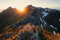 Summer midnight sun disspears behind mountain peak, Moskenesøy, Lofoten Islands, Norway