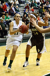 17 December 2011:  Karen Solari heads for the hoop defended by Michelle Karr during an NCAA womens division 3 basketball game between the St. Francis Fighting Saints and the Illinois Wesleyan Titans in Shirk Center, Bloomington IL