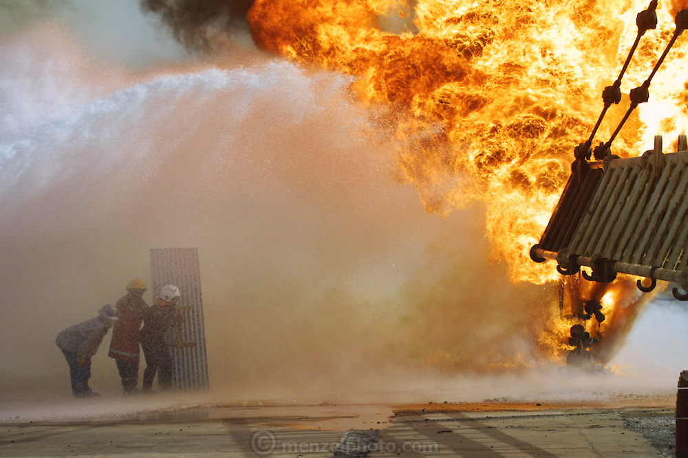 """Firefighters from the KWWK (Kuwait Wild Well Killers) attempt to kill an oil fire in the Rumaila field by guiding a """"stinger"""" that will pump drilling mud into the damaged well. A """"stinger"""" is a tapered pipe on the end of a long steel boom controlled by a bulldozer. Drilling mud, under high pressure, is pumped through the stinger into the well, stopping the flow of oil and gas. The Rumaila field is one of Iraq's biggest oil fields with five billion barrels in reserve. Many of the wells are 10,000 feet deep and produce huge volumes of oil and gas under tremendous pressure, which makes capping them very difficult and dangerous. Rumaila is also spelled Rumeilah."""