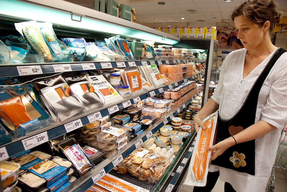 The Glad Ostensen family in Gjerdrum, Norway. Anne Glad Fredricksen, 45, chooses salmon while shopping for a week's worth of groceries. Model-Released.