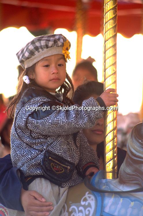 Girl age 5 riding carousel at Cinco de Mayo festival.   St Paul  Minnesota USA