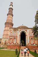 Tourists at the Qutub Minar and Alai Darwaza (Alai Gate), the entrance to the Quwwat-ul-Islam Mosque in Dehli, India