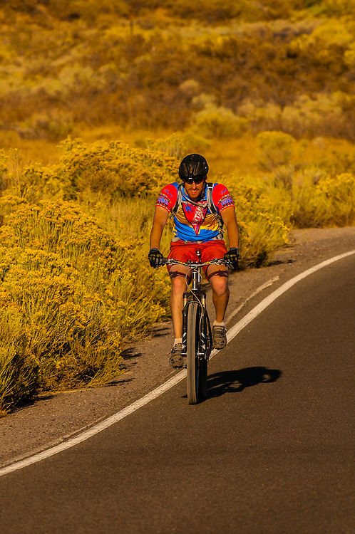 A bicyclist riding down the road on Simms Park Road, Albuquerque, New Mexico USA