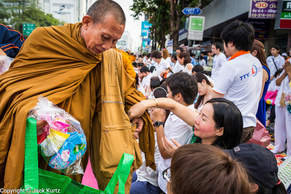 08 SEPTEMBER 2013 - BANGKOK, THAILAND: A woman makes merit by donating alms to a Buddhist monk during a mass giving ceremony in Bangkok Sunday. 10,000 Buddhist monks participated in a mass alms giving ceremony on Rajadamri Road in front of Central World shopping mall in Bangkok. The alms giving was to benefit disaster victims in Thailand and assist Buddhist temples in the insurgency wracked southern provinces of Thailand.       PHOTO BY JACK KURTZ