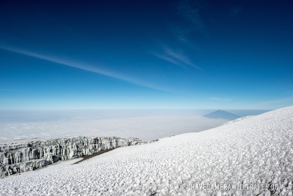 Snow and ice on the summit of Mt Kilimanjaro, with the summit of Mt Meru poking through the clouds in the distance at right.