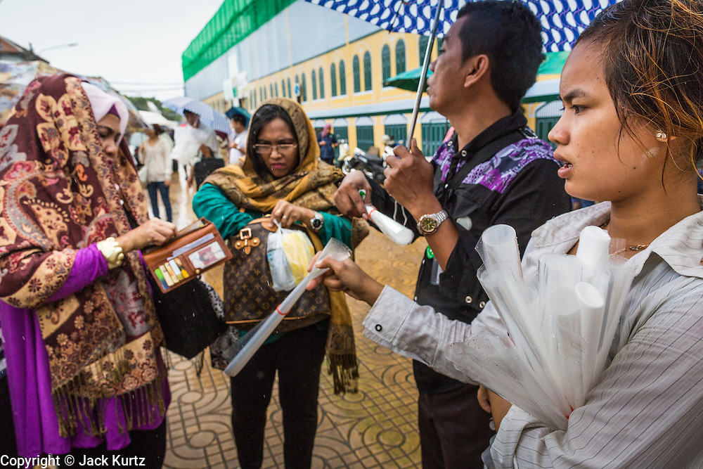 23 SEPTEMBER 2013 - BANGKOK, THAILAND: Tourists haggle with Thai vendors selling plastic bags to be worn as booties during street flooding in Bangkok. More than a quarter of the provinces in Thailand are reporting some flooding as heavy rainy season storms continue in central Thailand. Rain is expected to continue through this week, raising the possibility of serious flooding throughout the country. More than 600,000 Thais have been impacted by the flooding so far this year. Flooding in 2011 killed more than 800 people and cut economic growth for the year to just .10 percent.     PHOTO BY JACK KURTZ