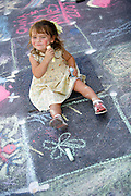 SHOT 6/24/2007 - Teagan Becker decides to use her face as a canvas after running out of room in the kids corner at the 5th annual Comcast La PIazza dell'Arte in Larimer Square in downtown Denver on Sunday June 24, 2007. The streets of the downtown historic district are transformed into a giant canvas as student, amateur and professional artists create temporary works of art on the asphalt. The event follows in the street painting traditions of 16th century Renaissance Italy where madonnari would recreate paintings of the Madonna on the streets with chalk..(Photo by Marc Piscotty / © 2007)