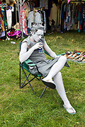 A man in grey body paint drink a beer through a straw at the Standon Calling Festival in Hertfordshire, UK.<br /> Standon Calling is a small independent festival set among the hills in Herfordshire that showcases World Music, Indie Music and dance Music. It is one of the new, small and quirky boutique festivals which have become popular in the UK.