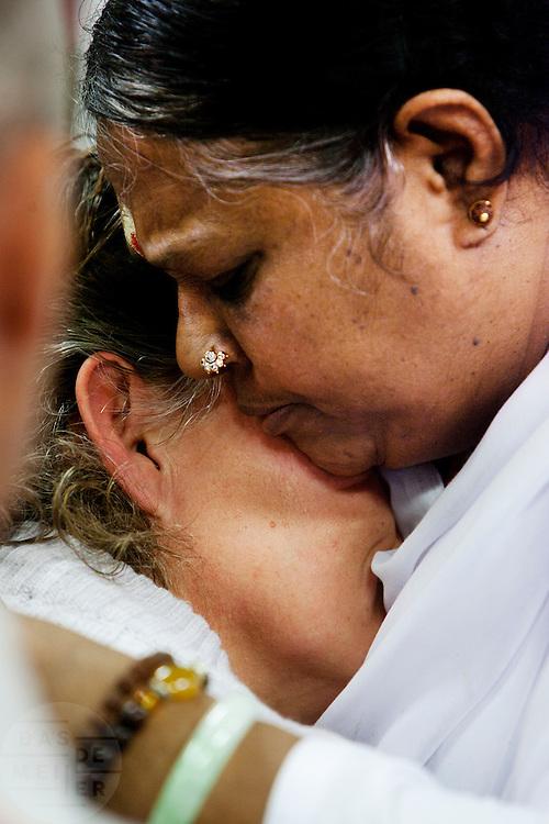 Een vrouw ondergaat de darshan, oftewel omhelzing van Amma. In de Expo in Houten is Mata Amritanandamayi, beter bekend als Amma of 'hugging mother', aanwezig om mensen te omhelzen en te inspireren. Het driedaags benefiet in Houten is het grootste spirituele festival in Nederland en zal naar verwachting 15.000 bezoekers trekken.<br /> <br /> A visitor is receiving the darshan from Amma. In the Expo in Houten people are gathering to get a darshan, or hug, by  Mata Amritanandamayi, also known as Amma or 'hugging mother'. Amma is travelling through the world to hug people for inspiring them to make a better world. Amma is one of the twelve most influence spiritual leaders of the world. The event in Houten lasts for three days and is the biggest spiritual event of The Netherlands.