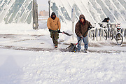 26 JANUARY 2021 - DES MOINES, IOWA: Workers clear a sidewalk in downtown Des Moines Tuesday morning following a heavy snow Monday. Workers in Des Moines started cleaning up a record snowfall Tuesday morning. The National Weather Service reports that 10.3 inches of snow fell at Des Moines International Airport Monday, January 25, breaking the daily record of 10 inches for January 25 set in 1895. Many downtown businesses closed for the day because of the snow, since roads throughout central Iowa were snowpacked and hard to drive.        PHOTO BY JACK KURTZ