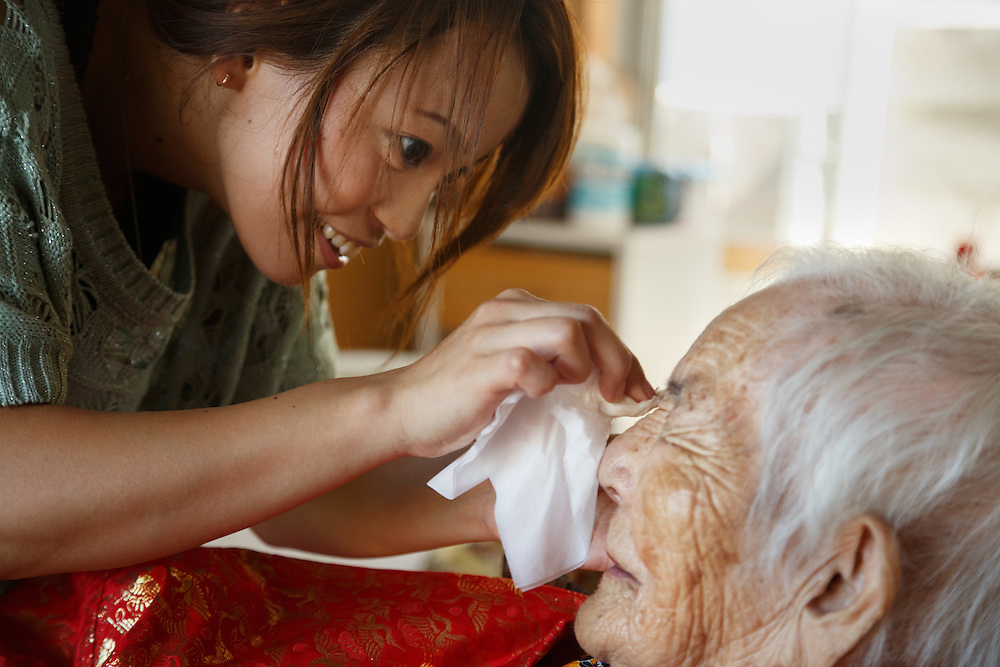 """Ayumi Naka helps her grandmother, 97-year-old Tomi Miyagi, prepare for a celebration in her honor at the town hall in Ogimi, Okinawa. In this village, an elderly resident's biggest celebration is reserved for one's 97th birthday, their """"kajimaya."""""""