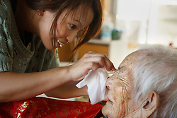 "Ayumi Naka helps her grandmother, 97-year-old Tomi Miyagi, prepare for a celebration in her honor at the town hall in Ogimi, Okinawa. In this village, an elderly resident's biggest celebration is reserved for one's 97th birthday, their ""kajimaya."""