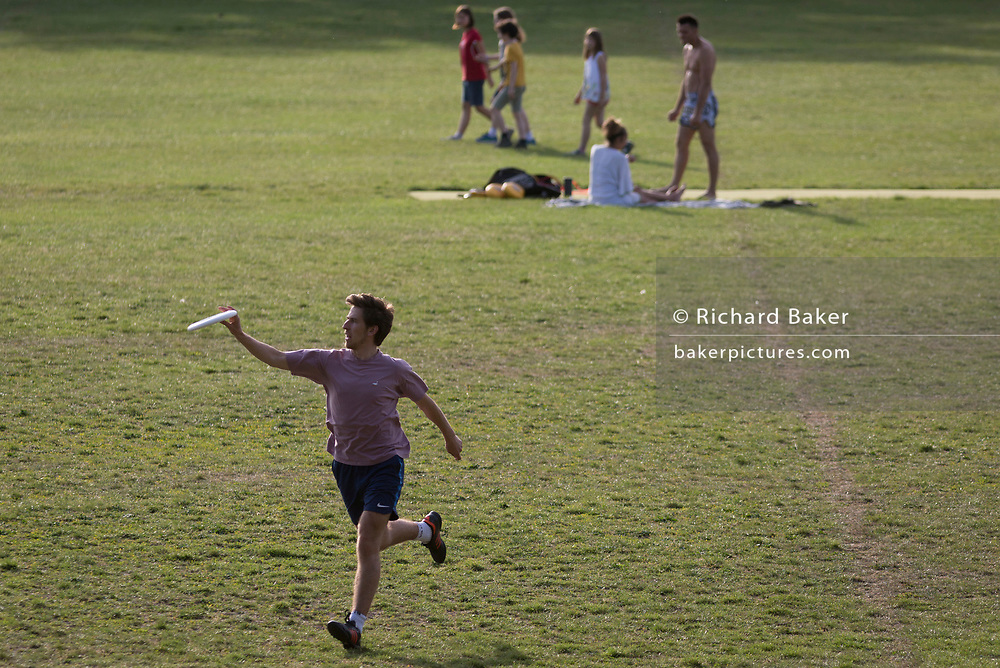 During the UK's Coronavirus pandemic lockdown and in the 24hrs when a further 255 deaths occurred, bringing the official covid deaths to 37,048, <br /> a Londoner catches a frisbee while social distancing in Ruskin Park, a public green space in the south London borough of Lambeth, on 26th May 2020, in London, England.