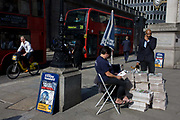 Evening Standard newspaper stand at Cornhill in the City of London. A businessman pauses while on his phone before picking up his copy of the free London paper before continuing his journey home, from this area in the heart of the capital's financial heart, known as the Square Mile. A cylist pedals past, a red double-decker bus on its way to Waterloo station is stopped in traffic and the Standard's vendor minds the piles of newsprint stacked on the pavement. The Evening Standard is owned by Russian-born proprietor, Evgeny Alexandrovich Lebedev.